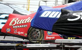 Covered NASCAR race cars sit on their trailers during a rain delay at the Bristol Motor Speedway in 2005.