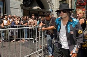 A Michael Jackson impersonator walks before crowds of fans waiting to pay their respects at Michael Jackson's star on the Hollywood Walk of Fame on Hollywood Blvd.