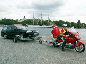 The tow vehicle may be a little unorthodox, but the tow dolly is a good choice -- it gets the drive wheels off the ground.