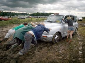 Festival goers try to push a taxi cab stuck in the mud at the Glastonbury Festival in Somerset, England. If only they had another towing vehicle with the right tow hooks … See more truck pictures.