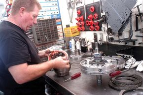 B.J. Allen takes apart a transmission at his business near Paducah, Ky.
