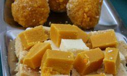 Squares of barfi wait on a tray of wedding treats.