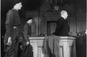 Surrounded by soldiers, a pale-faced Vidkun Quisling begins the legal battle for his life in a crowded court room in Oslo. He lost and was executed by firing squad for treason.