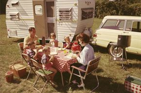 A family sits at a folding table eating a meal outside their station wagon and trailer, circa 1963.