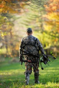 Hunter walking with tree stand and bow
