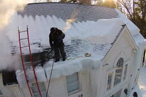 Dmitry Lipinsy, who owns Icedam Liquidators, uses a drone to see above a roof in Boston while Jesus Foentes uses steam to clear the ice off it.