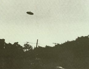 This photograph shows a UFO appearing above powerlines in a neighborhood.
