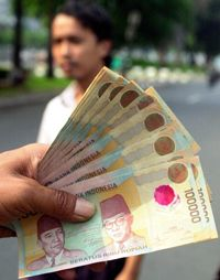 If you were stopped on the street and asked to split this money with the Indonesian man in the background, how much rupiah would you give him?