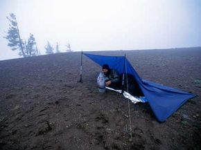 A hiker stops for a break under a tarp on the Pacific Crest Trail. A tarp is a lightweight shelter option.