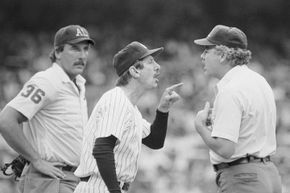New York Yankees manager Billy Martin (c) is shown arguing with umpire Tim McClelland over the amount of pine tar on the bat used by George Brett of the Royals, who got a two-run homer in the ninth inning. Brett came charging out of the dugout moments later.