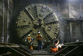 As workers follow a massive tunnel-boring machine, they put the finishing touches on the support structure for a train tunnel.