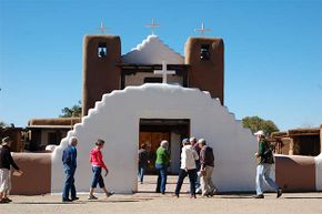 Visitors enter St. Jerome Church in Taos Pueblo, New Mexico. Taos is home to a bizarre noise known as the Taos Hum.
