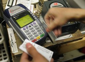 A sales associate works on a customer's transaction with a credit card at Cut Rate Toys Dec. 6, 2004 in Chicago.