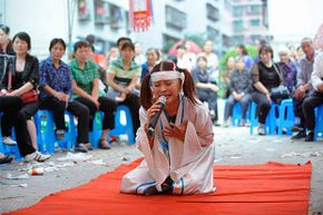 Professional mourner Hu Xinglian in action at a funeral in Chongqing, China. She comes to work with a full soundsystem, multi-color spotlights and the six members of her band.