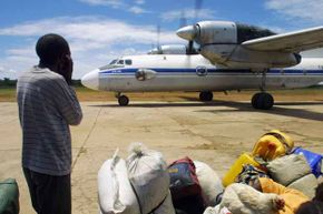 A former UNITA fighter covers his ears as a plane arrives to transport families displaced in Angola's brutal 27-year civil war which ended the year before in 2002.
