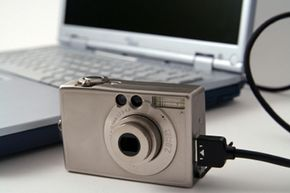 This photo shows a digital camera directly connected to a laptop using a USB cable. Some cameras use a USB-powered dock in which you insert the camera.