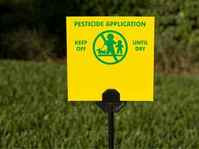 Pesticide sign on manicured lawn.