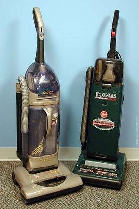 """Two upright vacuum cleaner models, one with the conventional bag system (right), and the other with the new """"cyclone"""" system (left)."""