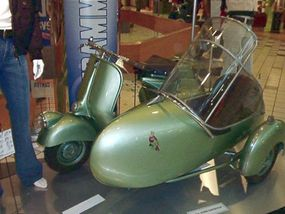 An original Vespa with a sidecar attached.