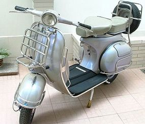 A classic Vespa with the spare tire mounted on the rear of the scooter.