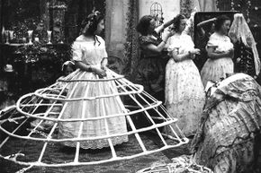 A crinoline-sporting woman waits for help before attempting to get dressed.