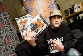 """Designer Mark Ecko holds up his new video game, """"Getting Up."""" Careers in video-game design are growing."""