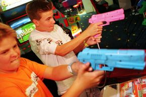 Two teen boys play Time Crisis II at an arcade.