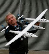 Sir Richard Branson with a model of WhiteKnightTwo and SpaceShipTwo