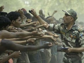 An officer puts a stamp on the arms of candidates during an Indian Army recruitment rally in Allahabad, India.