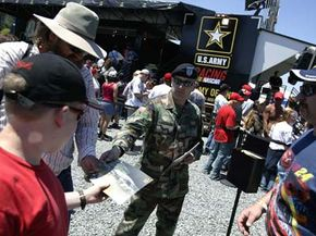 A U.S. Army recruiter hands out flyers to NASCAR fans in front of a mobile interactive recruiting exhibit in Charlotte, N.C.