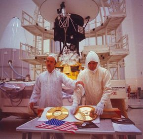 """""""Sounds of Earth"""" gold-plated record and U.S. flag prepared for storage aboard Voyager 2 spacecraft, with project manager John Cassini (left), at Kennedy Space Center."""