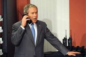 U.S. President George W. Bush speaks on a walkie-talkie during a tour of World Wide Technology, Inc. in 2008.