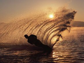 Water-skier at sunset sending up a spray of water