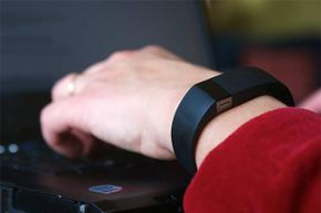 A worker types on his laptop while wearing Fitbit. A study showed less than half of Americans had privacy concerns about wearables in the workplace.