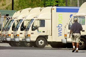 A WebVan employee cleans out some of the company's trucks outside its metro Atlanta distribution office in April 2001.