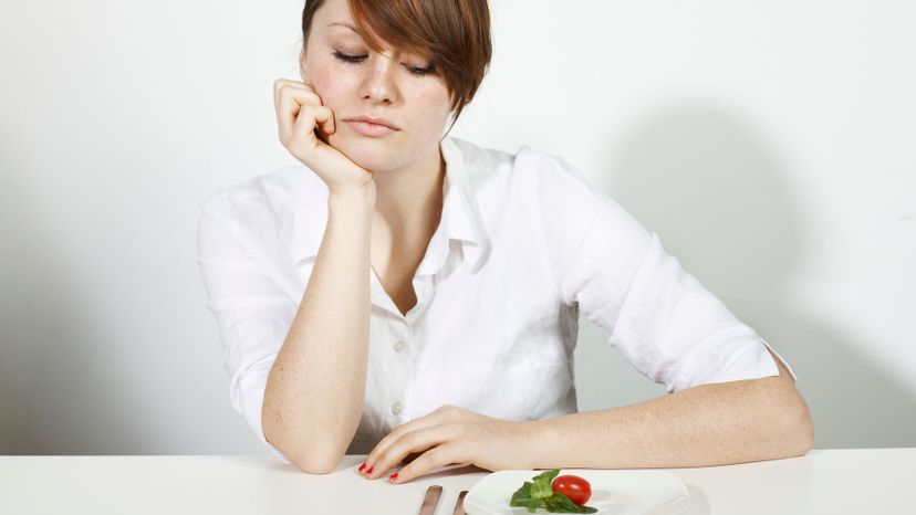 woman looking at a tiny plate of veggies.