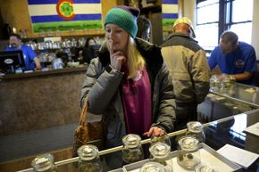 Kristin Brinckerhoff ponders the selection at 3D Cannabis Center, a retail marijana store, in Denver, Colo. In addition to all its other uses, scientists are researching marijuana's antibacterial properties.