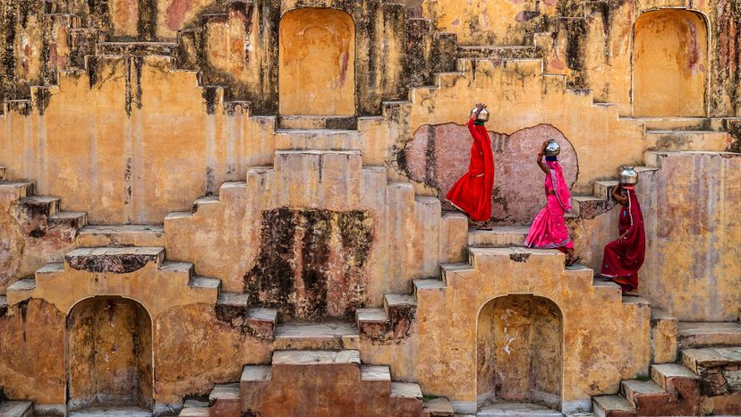 Indian women carry water from stepwell