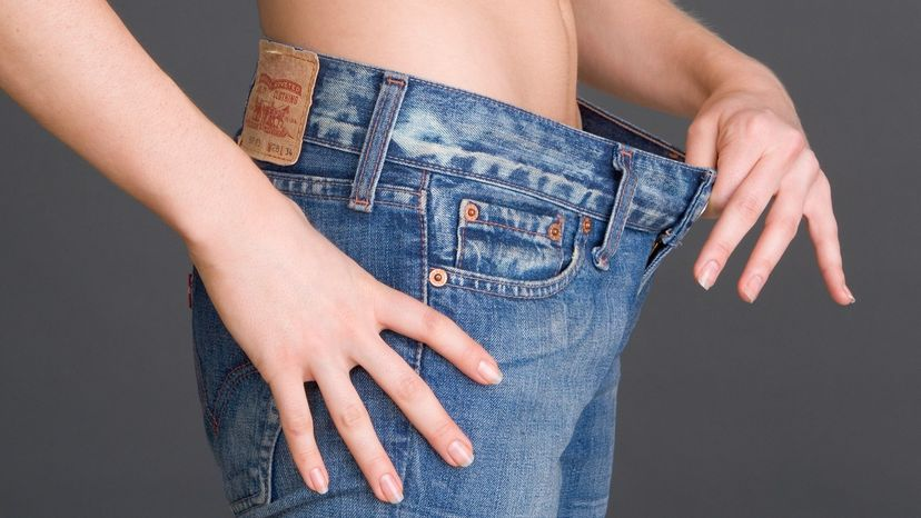 Woman holding loose waistband of jeans