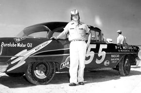 Junior Johnson poses on the beach with his #55 B&L Motors 1955 Oldsmobile before the Beach and Road Course race on Feb. 27, 1955, at the Beach and Road Course in Daytona Beach, Fla.