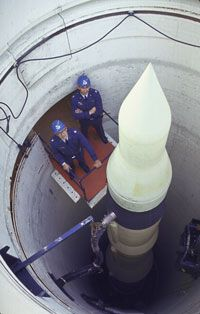 Two U.S. Air Force captains stand beside a Minuteman nuclear missile in a silo in 1964