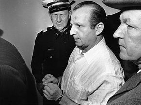 Jack Ruby, the man who shot Lee Harvey Oswald, is led away by police to his arraignment.