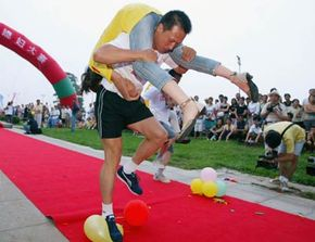 This wife-carrying contest participant is using the Estonian carry technique to wield his load.