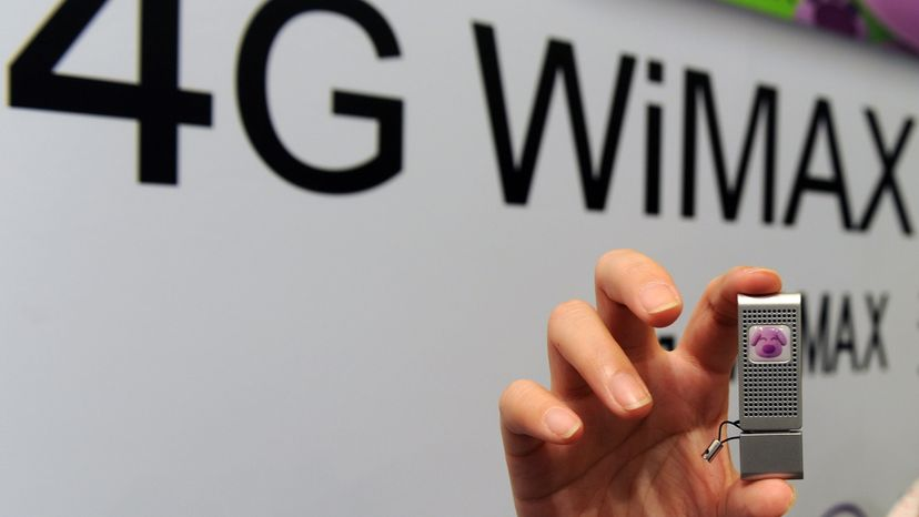 A woman displays a small silver fourth-generation WiMAX device