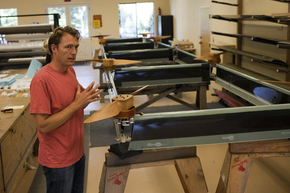 The founder of Joby Energy stands with his prototype of an airborne wind turbine.