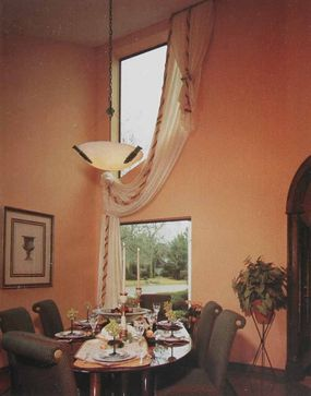 © An irregularly angled window above a standard rectangular window poses an opportunity for a little contemporary creativity. The drapery is trimmed with fabric-covered tubing and decorative cord.