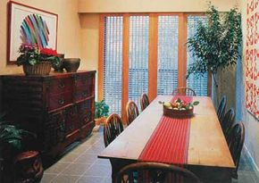 © This sliding wooden window grid echoes other geometric motifs in the dining room. The vertical lines of the framing boards repeat the linear sweep of the banquet table.