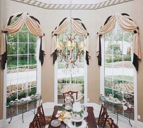 © Twist rods outlining the tops of these arched windows are covered in two formal fabrics, white satin and green moiré, perfect companions for the scarves atop them.