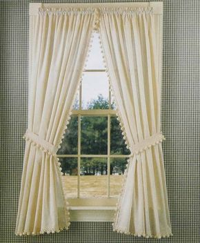 © One of country style's most appealing qualities is its ability to tug the heartstrings. This typical curtain in muslin tieback panels trimmed in ball fringe does just that.