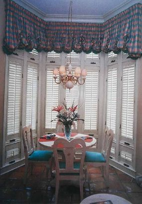 © This tall bay window combines wooden shutters of three different lengths. Bright white paint provides visual connection with the white dining table and chairs.